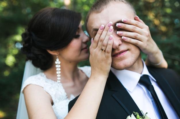 Charmante braut schließt die augen zu ihrem ehemann (von hinten)