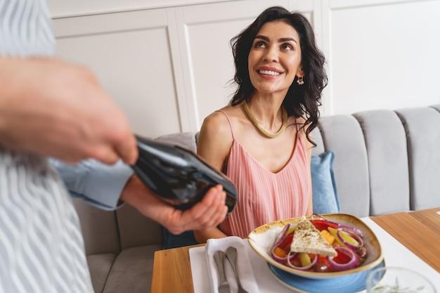 Charmante brünette dame, die café-arbeiter anschaut und lächelt, während der mann eine flasche alkoholisches getränk hält?