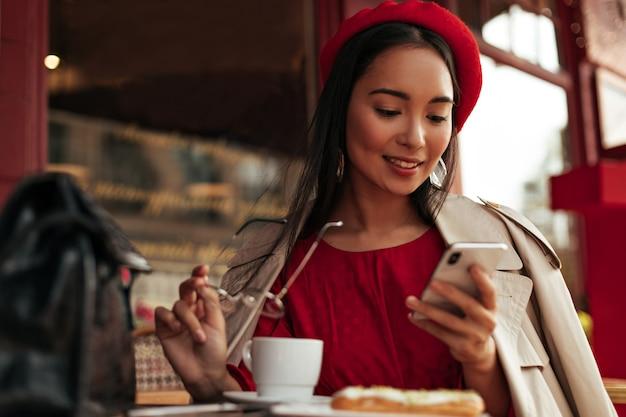 Charmante brünette frau in rotem barett, kleid und beigem trenchcoat lächelt, hält eine brille und entspannt sich im straßencafé