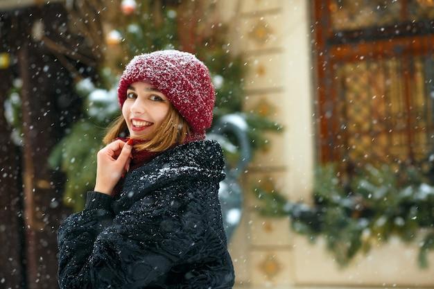 Charmante brünette frau mit roter mütze und schal, die schneefälle genießt. platz für text