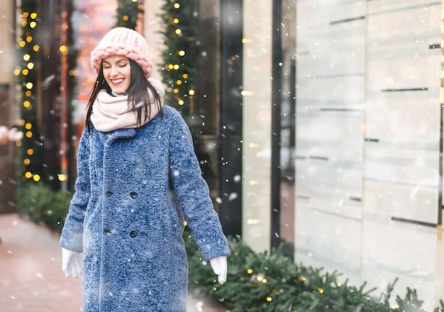 Charmante brünette frau trägt gestrickte hellrosa mütze und schal, die während des schneefalls durch die mit girlanden geschmückte stadt spaziert. platz für text