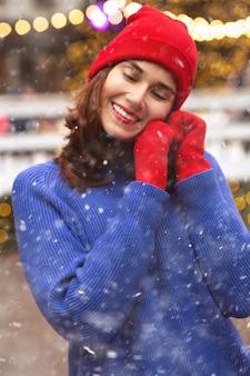 Charmante brünette frau trägt rote mütze und blauen pullover, die während des schneefalls auf dem weihnachtsmarkt auf dem zentralen stadtplatz spazieren geht