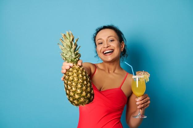 Charmante brünette mit schönem lächeln hält ein glas mit cocktail und zeigt der kamera eine ananas.