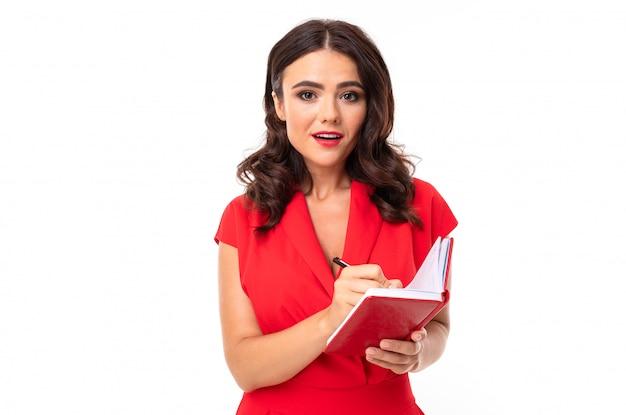 Charmante brünette sekretärin hört aufmerksam zu und schreibt auf ein notizbuch, gegen eine weiße wand in einem roten kleid
