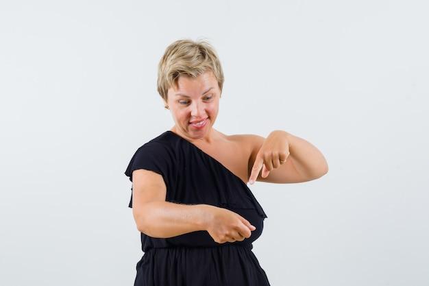 Charmante dame, die etwas hält, während sie es in der schwarzen bluse zeigt und konzentriert schaut