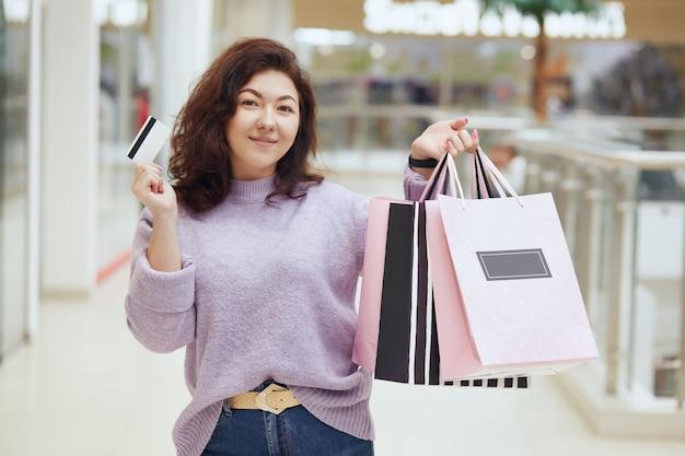 Charmante dame, die lila pullover hält, der kreditkarte und einkaufstaschen in händen hält, die im einkaufszentrum aufwerfen