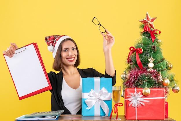 Charmante dame im anzug mit weihnachtsmannhut, der dokumente im büro auf gelbem lokalisiert hält