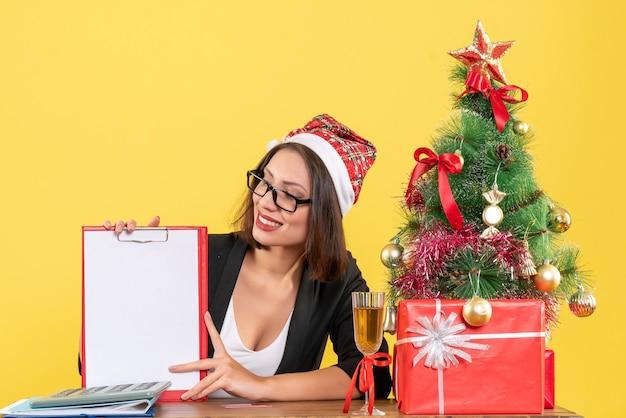 Charmante dame im anzug mit weihnachtsmannhut und brille, die dokument zeigt, das sich im büro glücklich fühlt