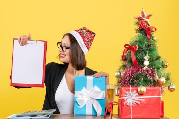 Charmante dame im anzug mit weihnachtsmannhut und brille, die dokumente hält, die geschenk im büro zeigen