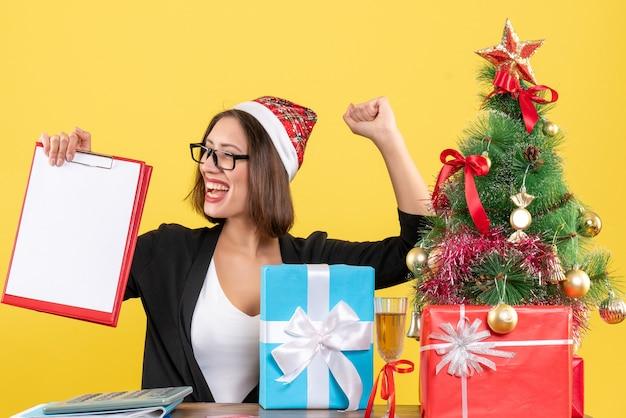 Charmante dame im anzug mit weihnachtsmannhut und brille, die dokumente stolz im büro hält