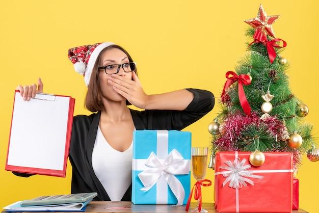 Charmante dame im anzug mit weihnachtsmannhut und brille, die überraschend dokumente im büro hält