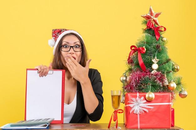 Charmante dame im anzug mit weihnachtsmannhut und brille zeigt dokument, das sich im büro überrascht fühlt