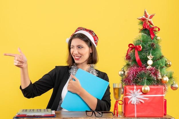 Charmante dame im anzug mit weihnachtsmannhut und neujahrsdekorationen, die dokument halten, das lustige reaktionen im büro auf gelb lokalisiert macht