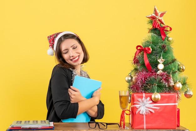 Charmante dame im anzug mit weihnachtsmannhut und neujahrsdekorationen, die dokument umarmen und im büro auf gelb isoliert träumen