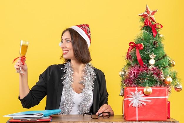 Charmante dame im anzug mit weihnachtsmannhut und neujahrsdekorationen, die wein im büro auf gelb lokalisiert erheben
