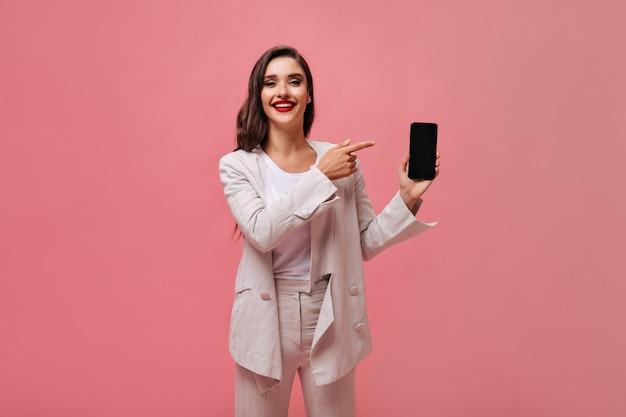 Charmante dame im beige anzug demonstriert smartphone auf rosa hintergrund. stilvolle frau mit hellem make-up im weißen outfit zeigt auf ihrem handy.