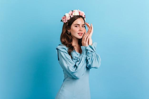 Charmante dame im eleganten blauen kleid, das auf isolierter wand aufwirft. innenporträt der jungen frau mit rosa blumen im dunklen haar.