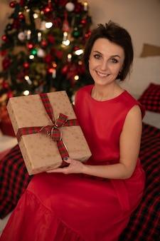 Charmante dame im roten kleid lächelnd, während sie ein geschenk hält, das in bastelpapier eingewickelt ist und auf bett sitzt