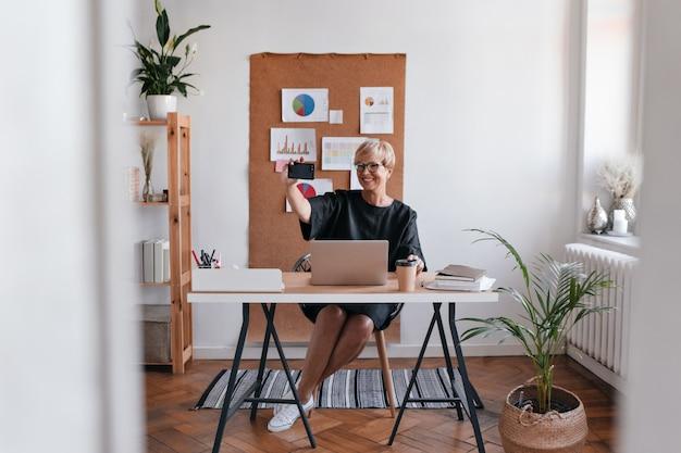 Charmante dame im schwarzen kleid nimmt selfie im büro