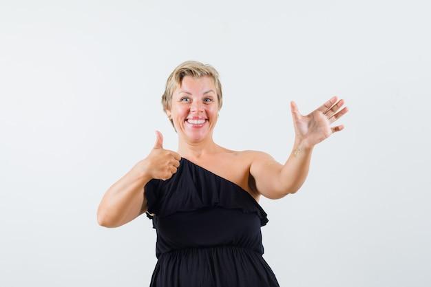 Charmante dame in der schwarzen bluse, die wie das halten des telefons aufwirft, während daumen zeigt und optimistisch aussieht