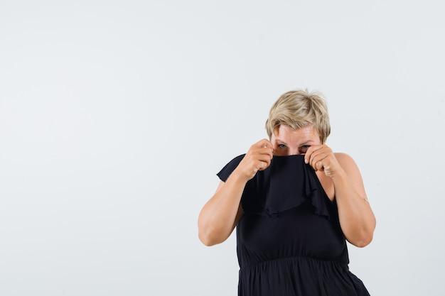 Charmante dame in schwarzer bluse, die den kragen an der nase anhebt und angewidert aussieht