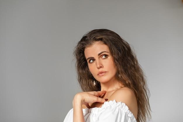 Charmante dame mit make-up und welligen brünetten haaren in weißem top mit nackten schultern, die nachdenklich die hand an der brust halten. auf grauem hintergrund isolieren. studioaufnahme.