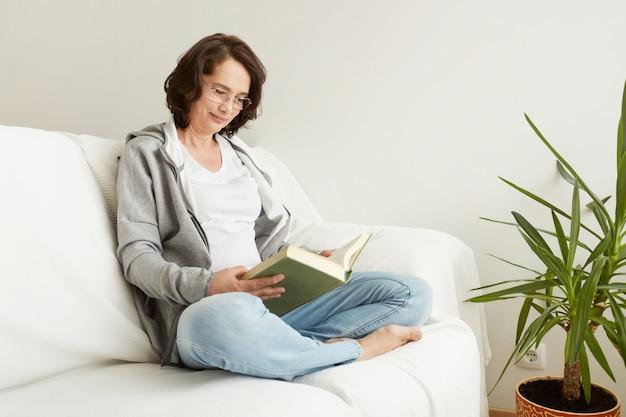 Charmante dame mittleren alters, die es genießt, zu hause zu sein und zu lesen