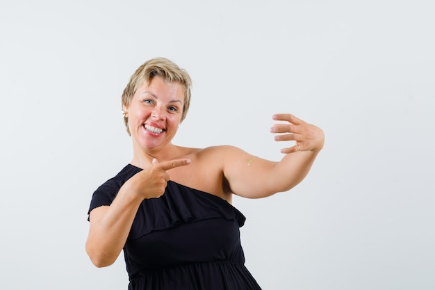 Charmante dame posiert wie auf telefon in schwarzer bluse zeigen und zufrieden aussehen