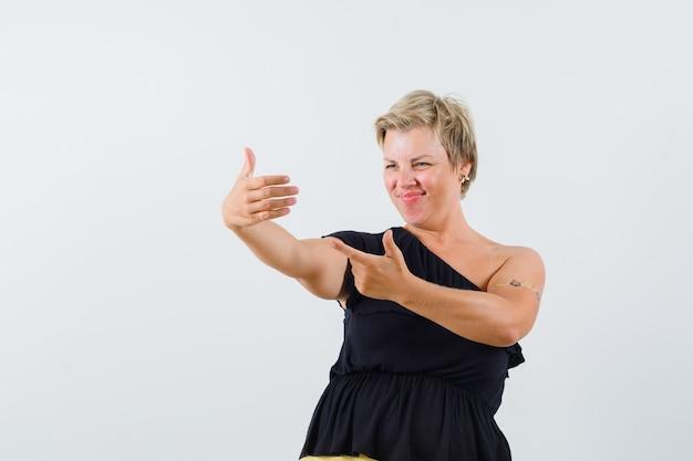 Charmante dame posiert wie das schauen ihres fotos am telefon in der schwarzen bluse und sieht erfreut aus