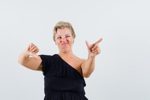 Charmante dame posiert wie telefon halten, während daumen in schwarzer bluse nach unten zeigt und missfallen aussieht. vorderansicht.