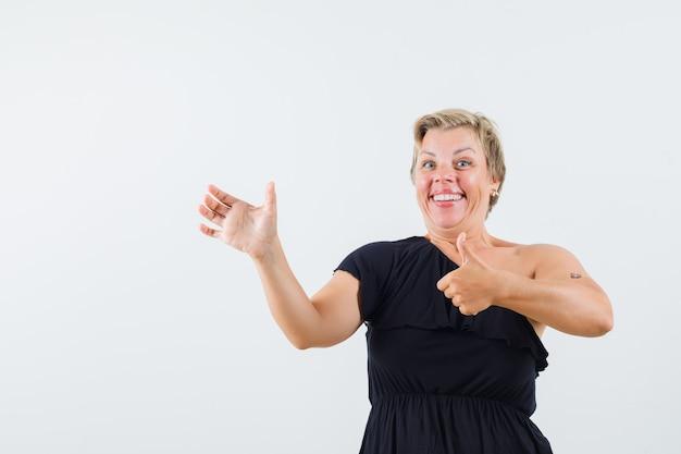 Charmante dame posiert wie telefon halten, während daumen in schwarzer bluse zeigt und lustig aussieht. vorderansicht.