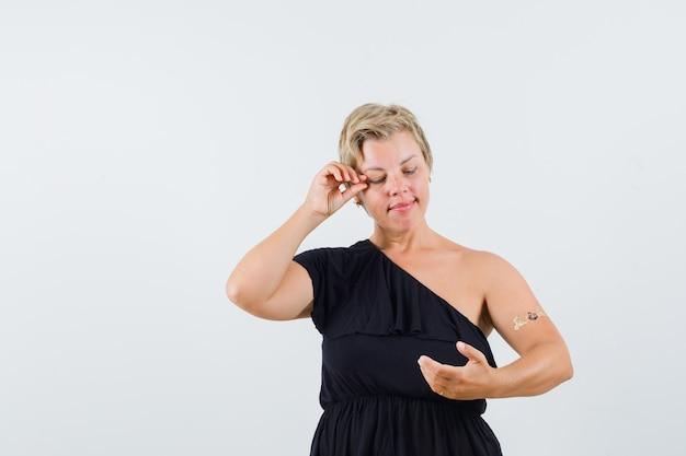 Charmante dame posiert wie telefon in schwarzer bluse halten und erfreut aussehen. vorderansicht.