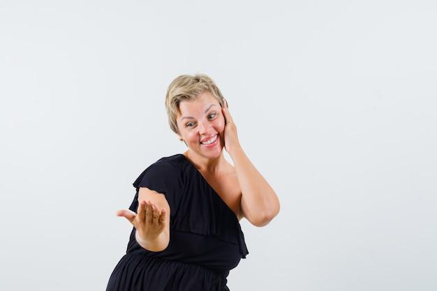 Charmante dame posiert wie telefonieren in schwarzer bluse und sieht froh aus. vorderansicht.