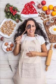 Charmante dunkelhaarige köchin versteckt ihr auge hinter dem holzlöffel und liegt auf dem boden und ist umgeben von lebkuchen, eiern, mehl auf einem holztisch, weihnachtsmütze, getrockneten orangen und backformen.