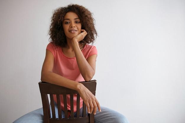 Charmante dunkelhäutige lockige dame, die auf stuhl sitzt und mit der hand chining, mit sanftem lächeln schauend, posierend