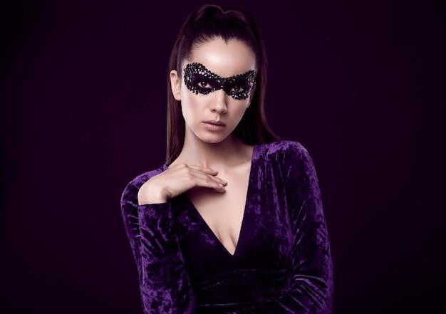 Charmante elegante brünette frau in lila kleid und pailletten maske