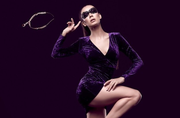 Charmante elegante brünette frau in schönen lila kleid und pailletten maske