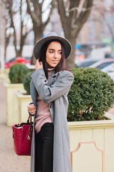 Charmante elegante junge frau im langen grauen mantel, hut, der im stadtzentrumspark geht. luxusausblick, rote tasche, fröhliche stimmung, lächeln zur seite, wahre emotionen.