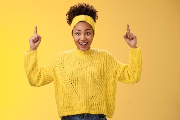Charmante, emotionale junge afroamerikanische frau in pullover-stirnband, die beeindruckende summen geld gewinnt, die nach oben zeigende zeigefinger zeigen, die den link zeigen, überrascht, überrascht, breit gelber hintergrund.