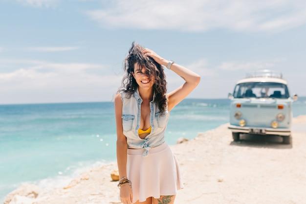Charmante entzückende frau gekleidet mit jeanshemd und rock genießt ihren urlaub am strand