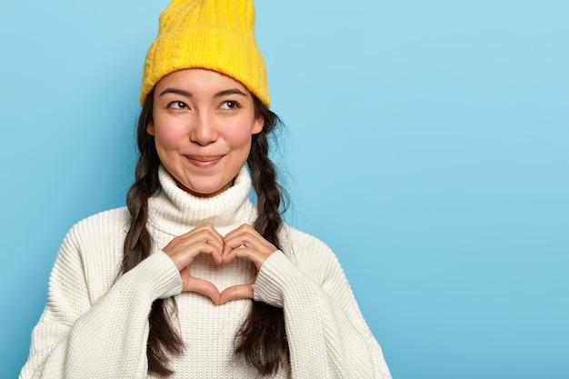 Charmante erfreute junge asiatische frau macht herzzeichen, gesteht freund in der liebe, hat gesichtsausdruck erfreut, schaut zur seite, trägt gelben hut und pullover
