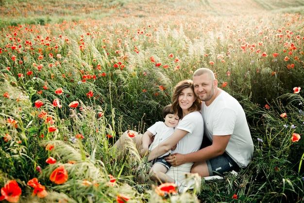 Charmante familie sitzt zwischen den mohnblumen