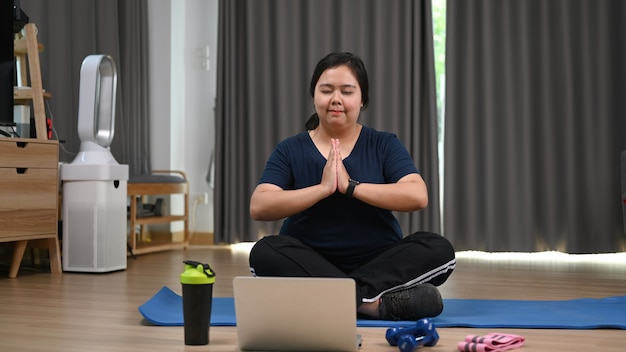 Charmante fettleibige frau praktiziert yoga mit laptop zu hause.
