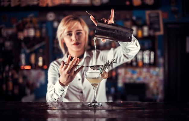 Charmante frau barkeeper mischt einen cocktail an der theke Premium Fotos