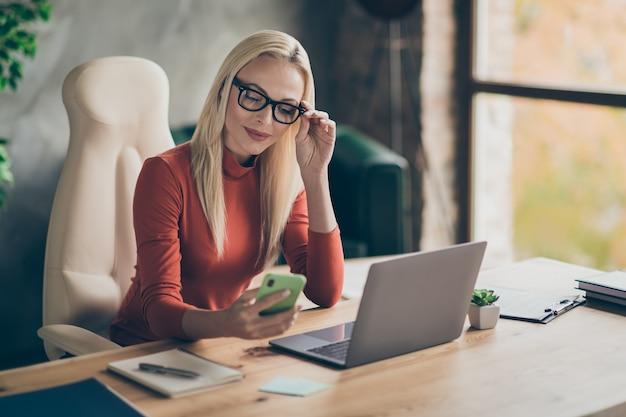 Charmante frau chef chef trägt orange rollkragen sitzen tisch erhalten social media benachrichtigung lesen sms von kunden im büro tragen roten rollkragenpullover