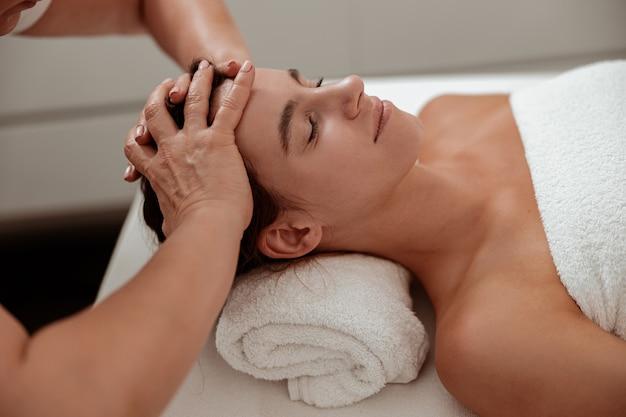 Charmante frau, die eine professionelle kopfhautmassage im spa-salon erhält