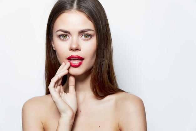 Charmante frau hält hand in der nähe von gesicht rote lippen saubere haut nackte schultern