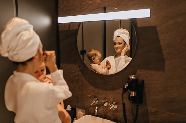 Charmante frau im bademantel setzt make-up und hält baby. mutter und tochter beobachten die morgenroutine im badezimmer.