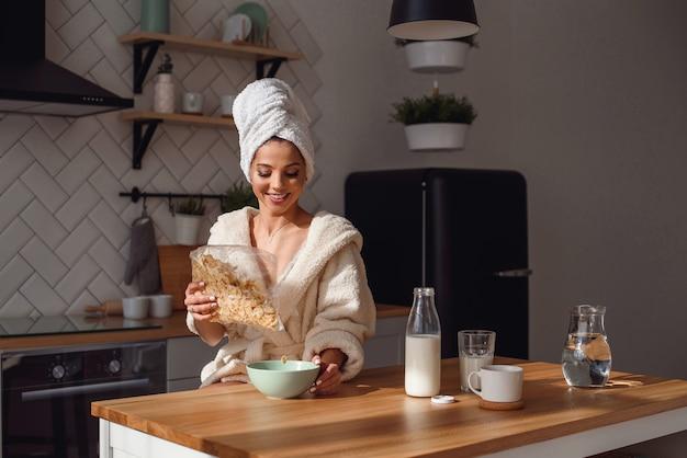 Charmante frau im bademantel und handtuch auf dem kopf bereitet ein gesundes frühstück mit flocken und milch. das mädchen frühstückt morgens in der stilvollen, gemütlichen küche.