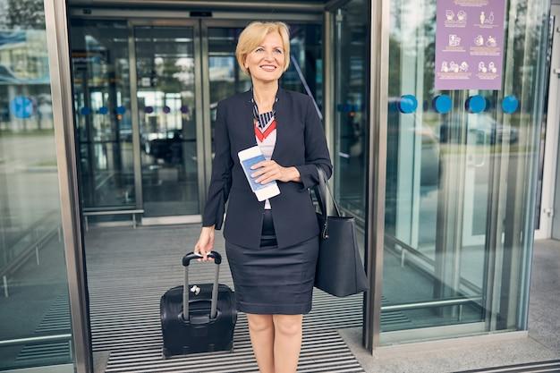 Charmante frau im eleganten rockanzug mit reisekoffer und lächelnd beim verlassen des flughafenterminals
